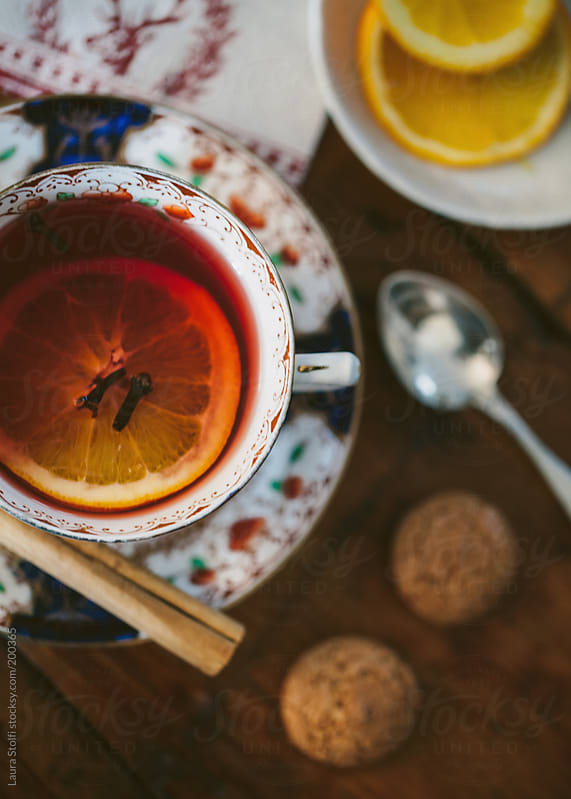 Wintry red fruits tea with cinnamon stick, lemon slices, cloves  and cookies by Laura Stolfi for Stocksy United