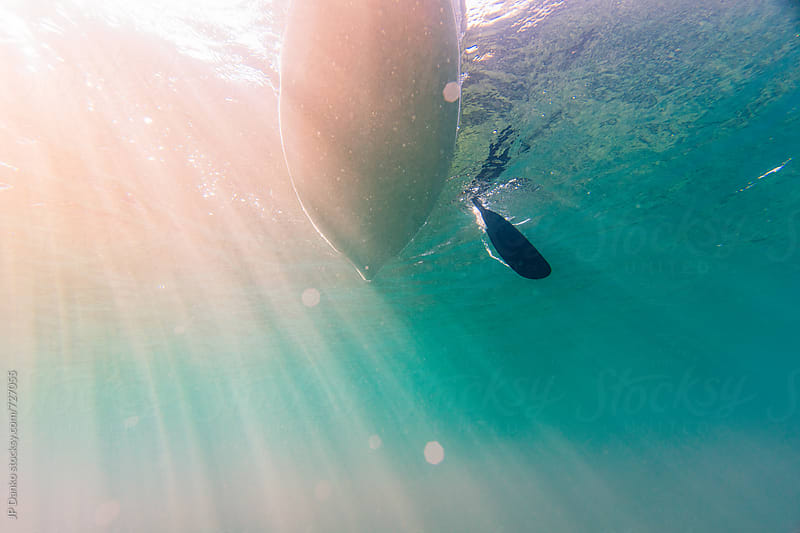 Underwater Photo of Kayak Passing Overhead with Paddle and Sun Flare in Lake at Family Cottage by JP Danko for Stocksy United