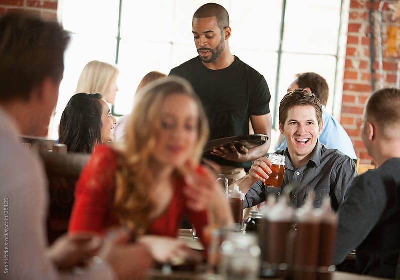 Barbeque: Happy Guy with Friends in Busy Restaurant by Sean Locke for Stocksy United