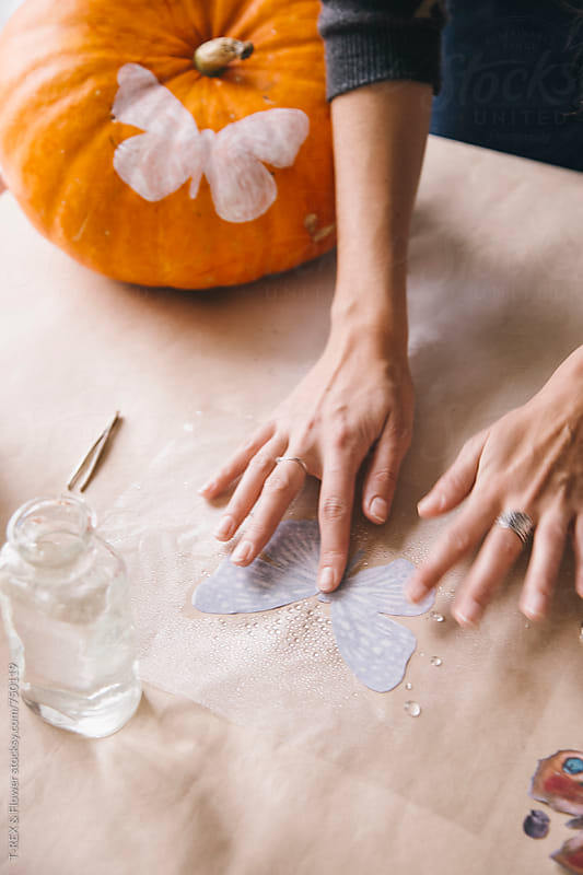 Woman preparing overlay for pumpkin by Danil Nevsky for Stocksy United