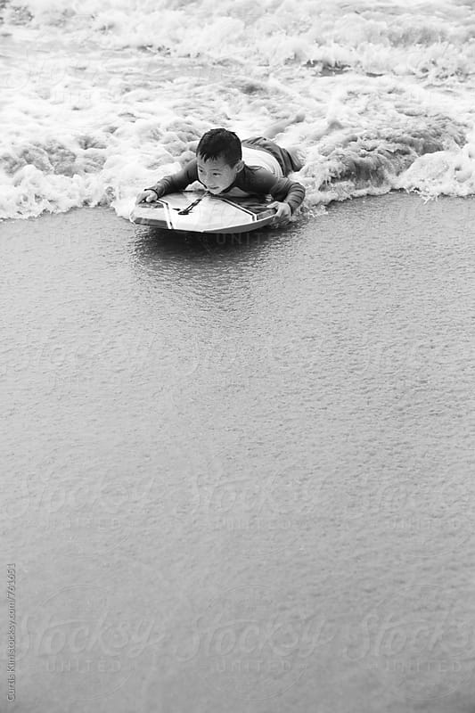 Little boy riding a boogie board on shore by Curtis Kim for Stocksy United