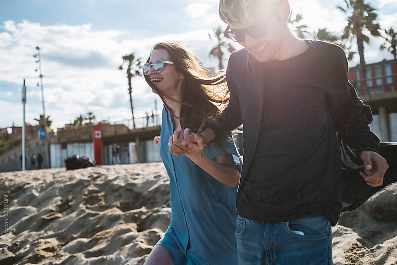 Young couple having fun at the beach by GIC for Stocksy United