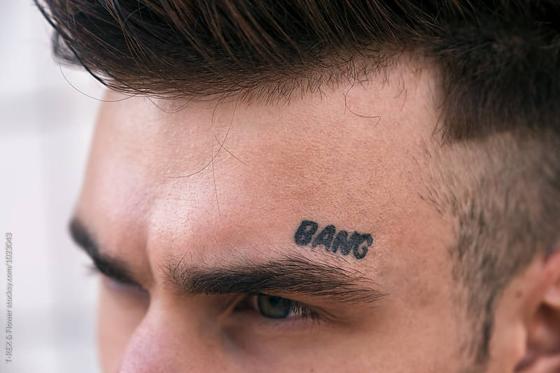Close-up of man's forehead with bang tattoo by T-REX & Flower for Stocksy United