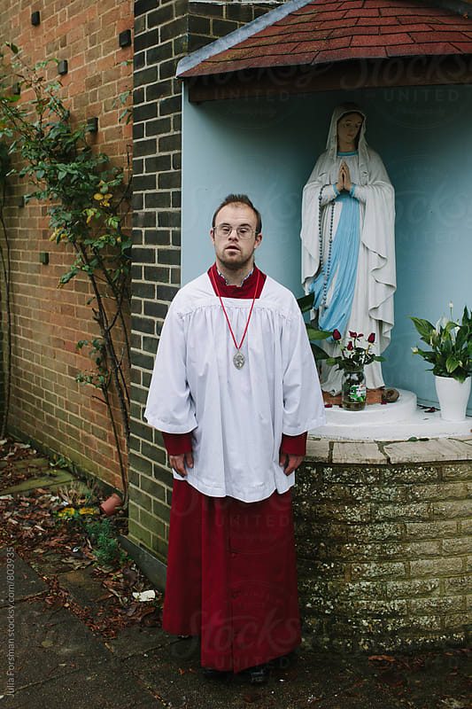 A man with Down's Syndrome wearing altar serving robes poses next to a statue of the Virgin Mary. by Julia Forsman for Stocksy United
