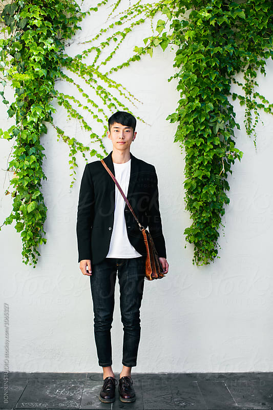 Portrait of an asian businessman standing in front of an ivy wall by BONNINSTUDIO for Stocksy United