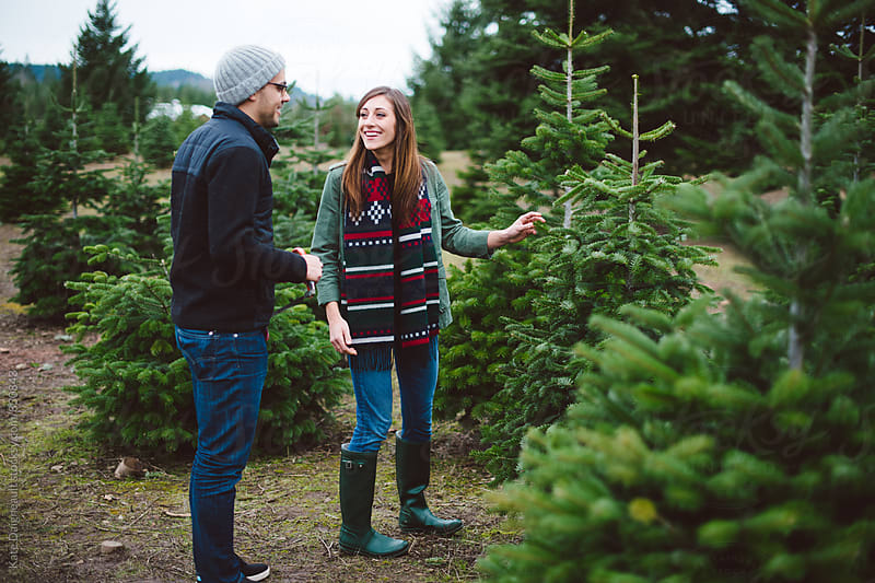 Attractive young couple cutting down their Christmas tree. by Kate Daigneault for Stocksy United
