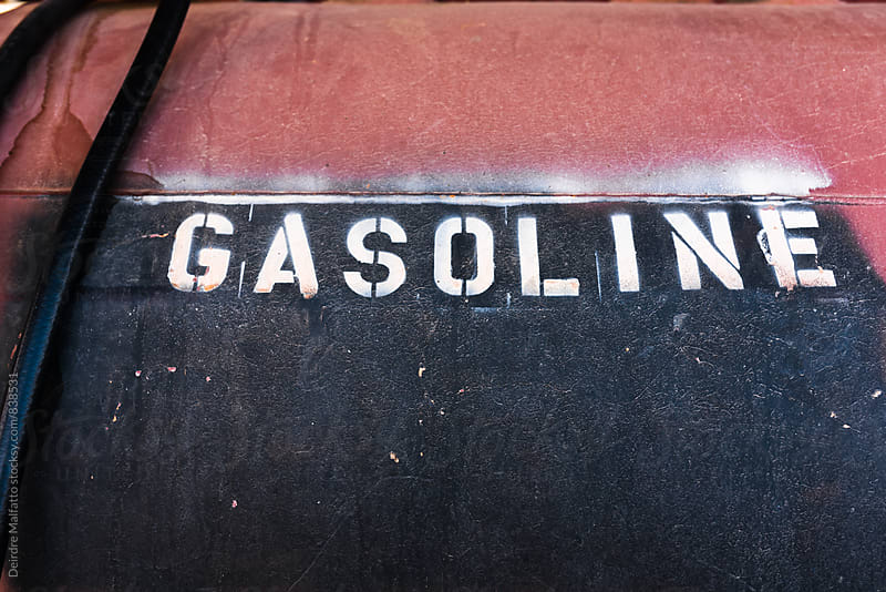 the word gasoline stenciled on an old tank by Deirdre Malfatto for Stocksy United