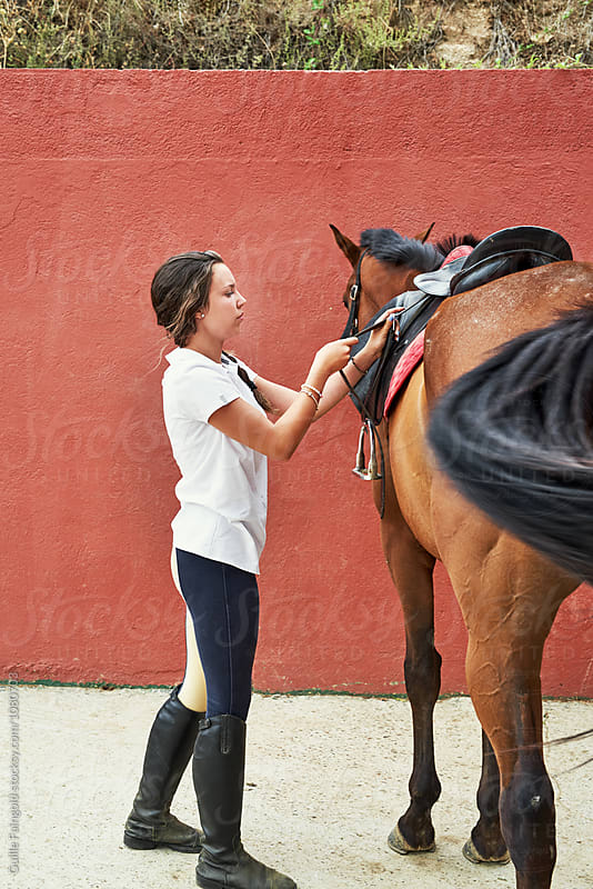 Brunette jockey with braid wearing saddle on horse back by Guille Faingold for Stocksy United