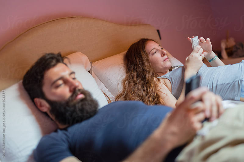 Couple in the bedroom holding cellphone by Good Vibrations Images for Stocksy United