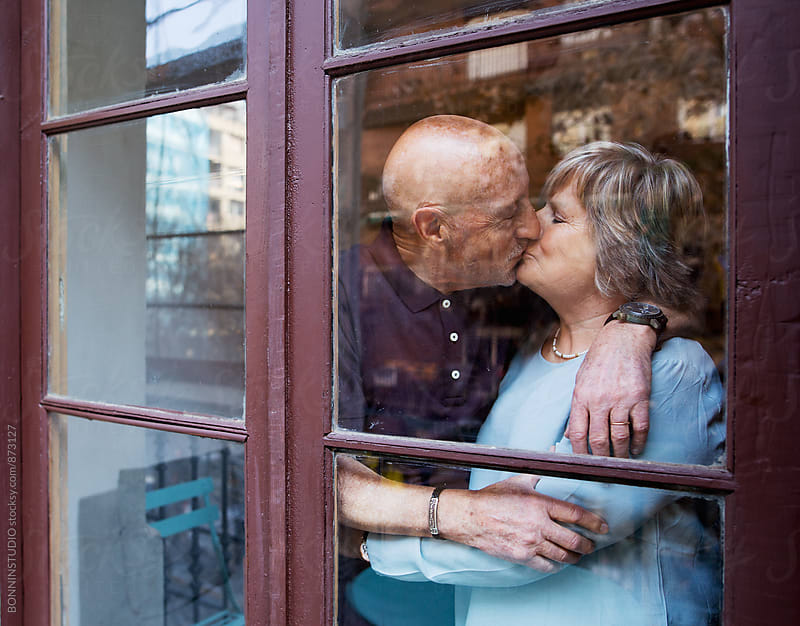 Elderly couple kissing standing through the window. by BONNINSTUDIO for Stocksy United