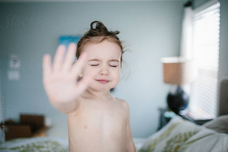 A cute toddler standing on a bed showing the palm of her hand by Jakob for Stocksy United