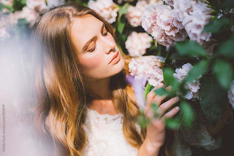 Beautiful Blue-eyed Woman in a Tropic Garden  by Marija Savic for Stocksy United