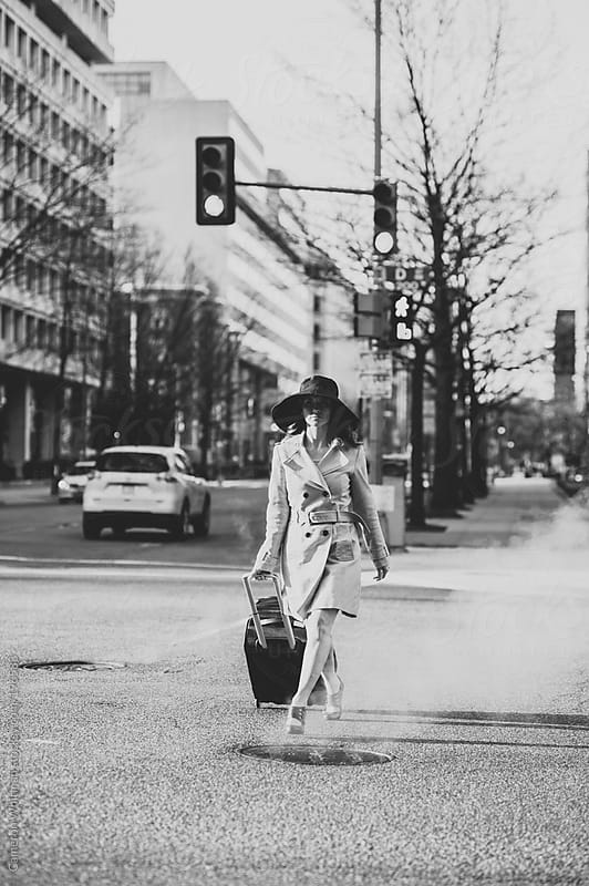 Attractive woman crossing the street with luggage  by Cameron Whitman for Stocksy United