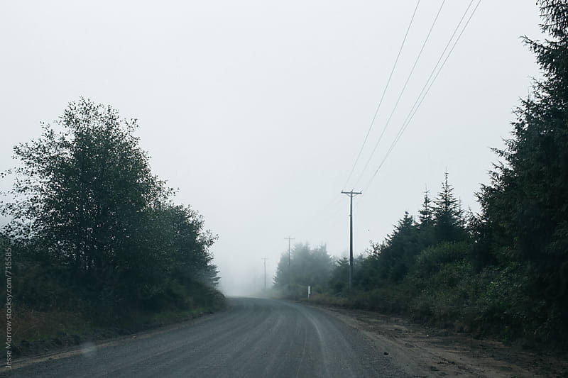 dark scary road with fog  by Jesse Morrow for Stocksy United