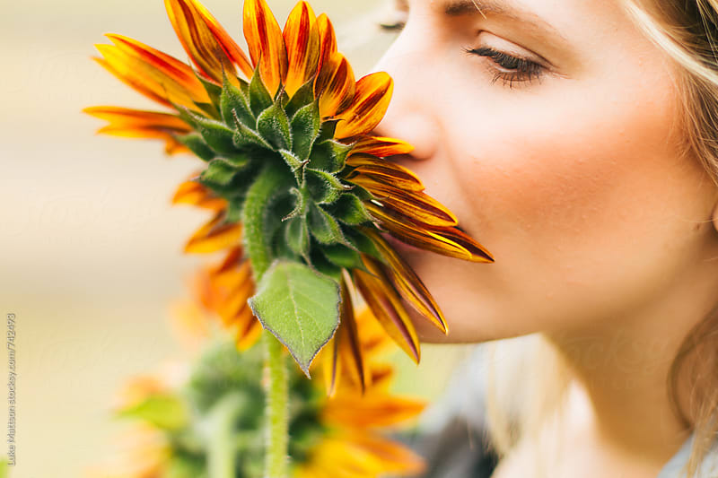 Young Blonde Woman Smelling A Red Sunflower by Luke Mattson for Stocksy United