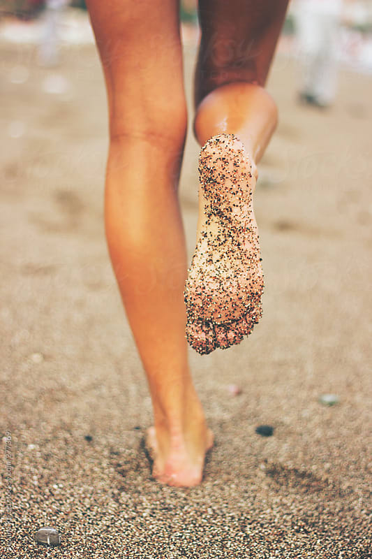 Female feet on the beach covered in sand by Jovana Rikalo for Stocksy United