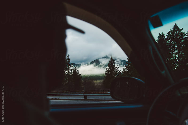 View of a cloudy mountain out the drivers side window. by Kate Daigneault for Stocksy United