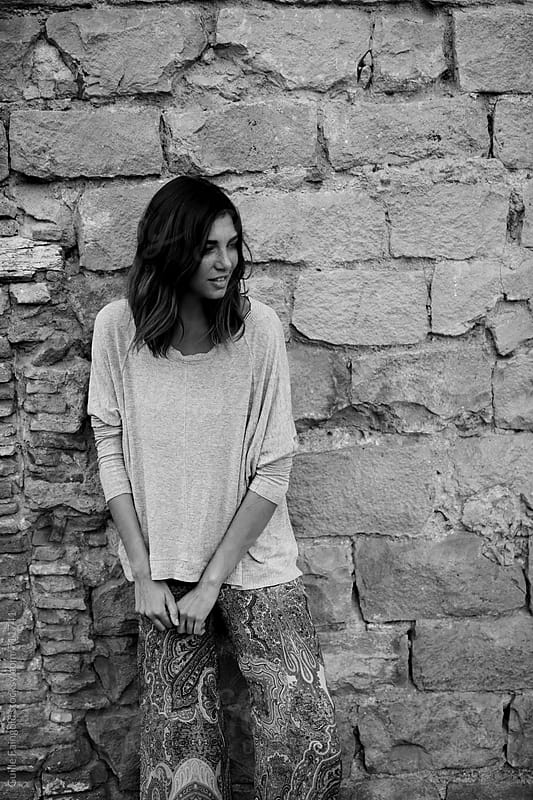 stylish brunette woman against stone wall by Guille Faingold for Stocksy United
