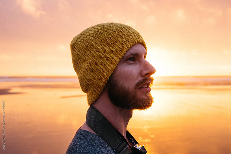 side profile portrait of young male at beach during sunset by Jesse Morrow for Stocksy United