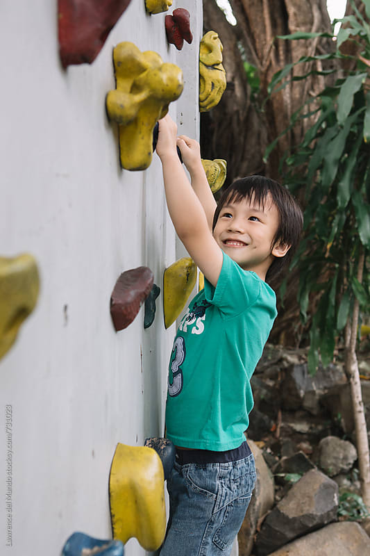 A very young kid visibly happy after making it near the farthest end of the wall by Lawrence del Mundo for Stocksy United
