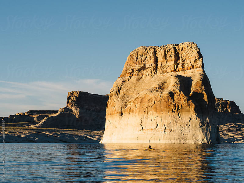 Anonymous girl on float in middle of lake with rock formation. Utah. by Jeremy Pawlowski for Stocksy United
