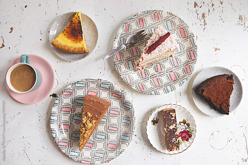 overhead view of cakes and slices for afternoon tea on vintage plates by Natalie JEFFCOTT for Stocksy United