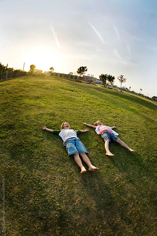 Fisheye View of Boy and Girl Laying In Grass by Dina Giangregorio for Stocksy United