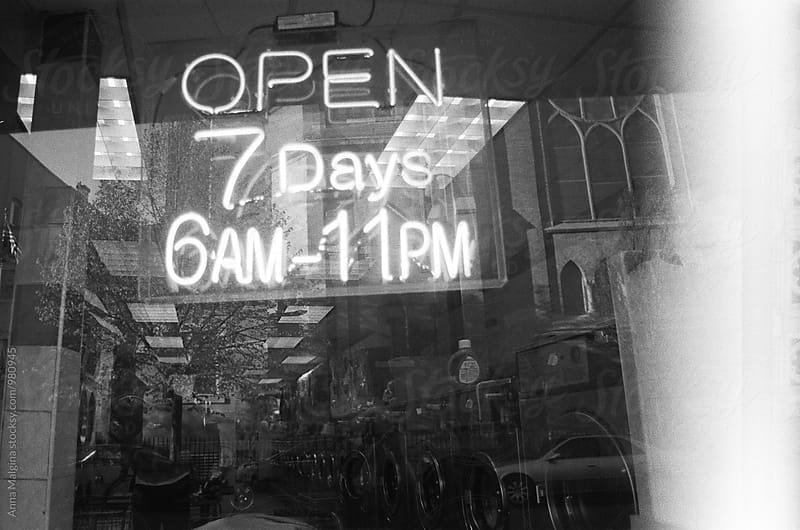 The black and white film photo of opening hours neon sign by Anna Malgina for Stocksy United
