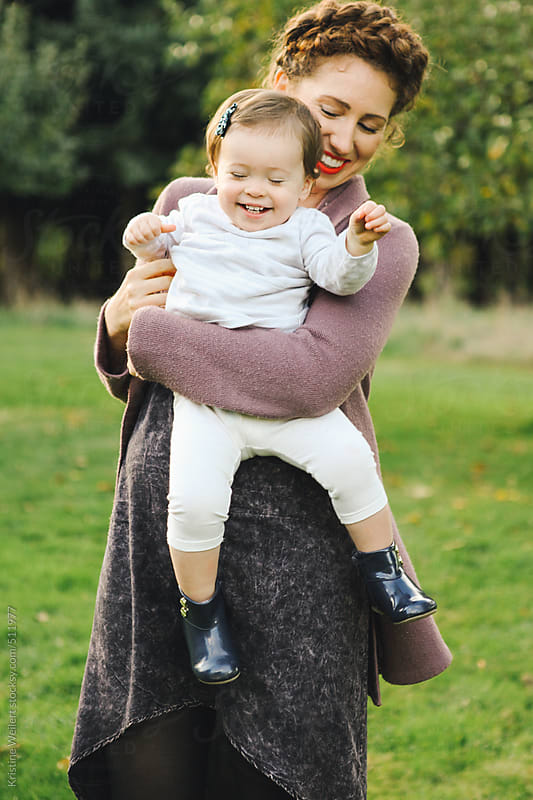 Beautiful mother holding smiling toddler daughter by Kristine Weilert for Stocksy United