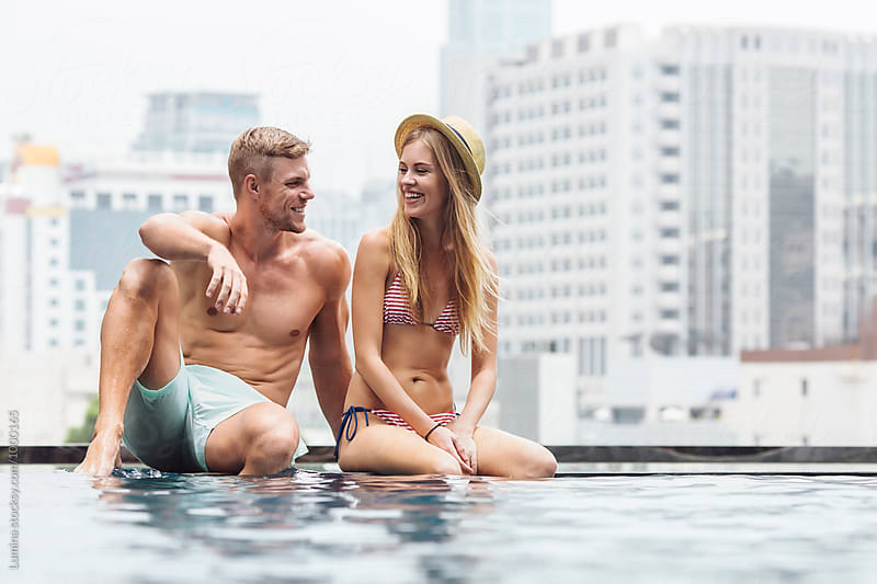 Happy Couple Relaxing in a Swimming Pool by Lumina for Stocksy United