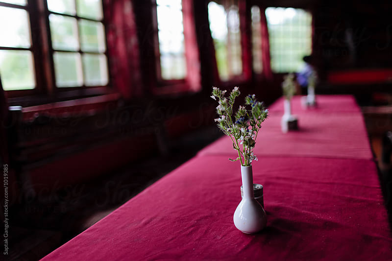 Flower vase with flowers on a table inside a rural restaurant by Saptak Ganguly for Stocksy United