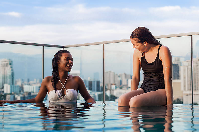 Two girlfriends relaxing at swimming pool with city skyline behind them. by Marko Milanovic for Stocksy United