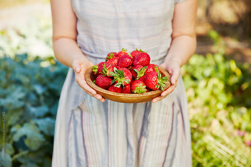Woman farmer holding fresh strawberries from her garden by Trinette Reed for Stocksy United