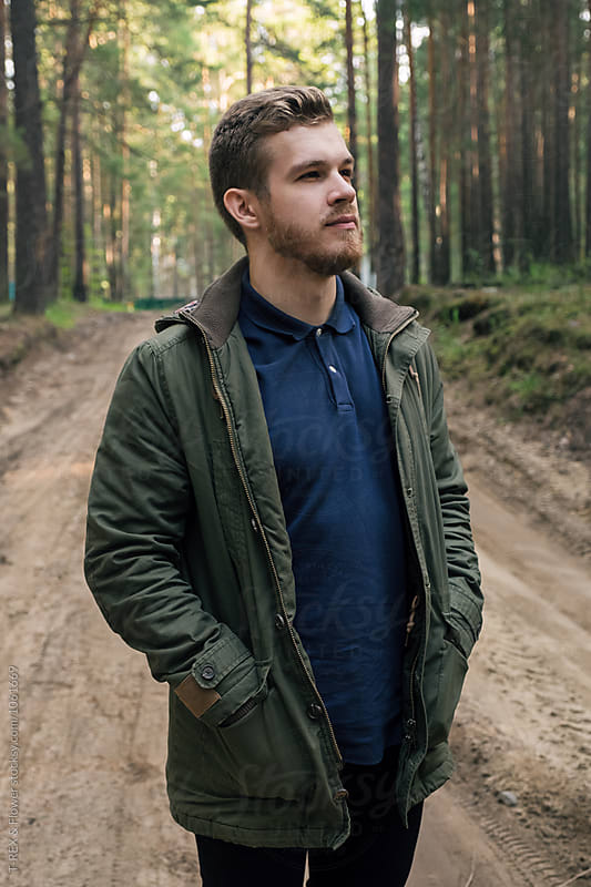 Handsome pensive man looking away in forest by Danil Nevsky for Stocksy United