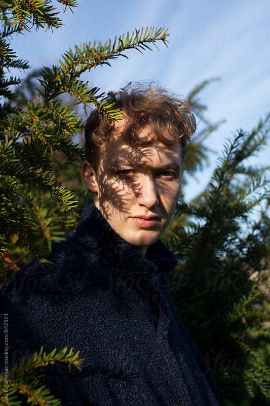 Serious, beautiful young man standing next to fir tree. There are shadows falling across his eyes. by Julia Forsman for Stocksy United