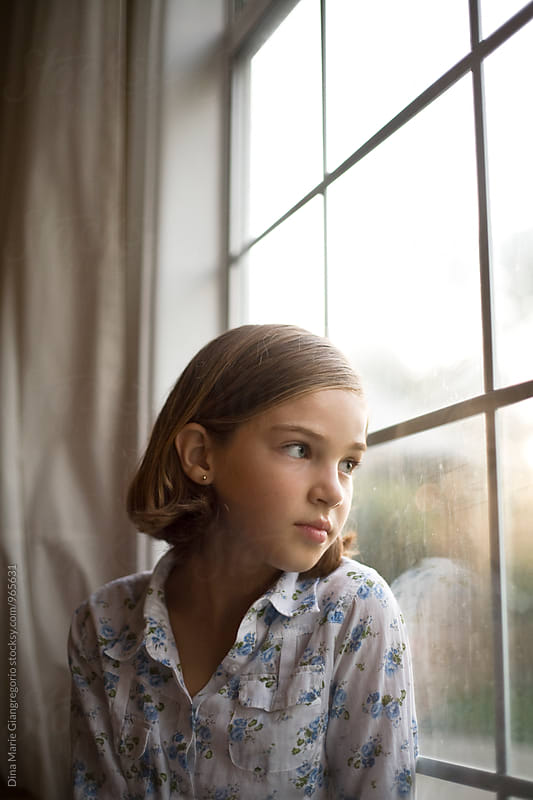 Young Girl Looking Out Tall Window by Dina Giangregorio for Stocksy United