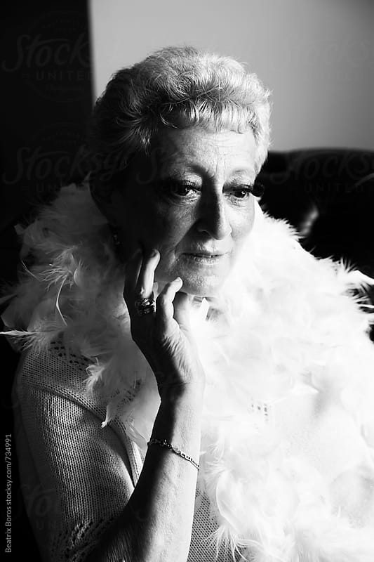 Portrait of a feminine senior woman wearing feather by Beatrix Boros for Stocksy United
