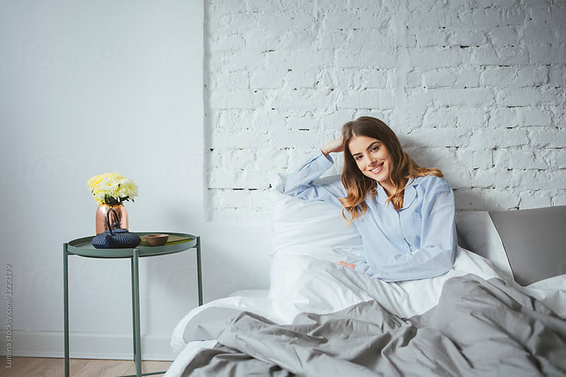 Portrait of Beautiful Woman Sitting on Her Bed by Lumina for Stocksy United