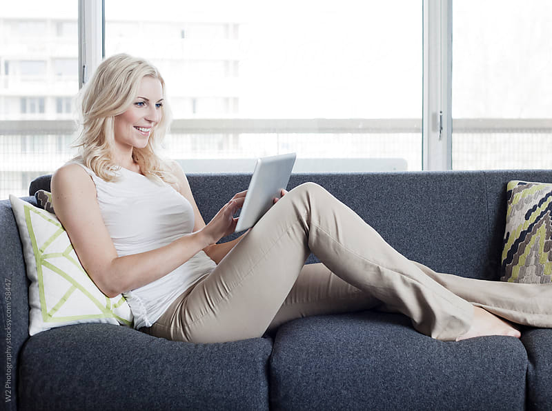 Beautiful woman with a tablet PC, relaxing on the couch. by W2 Photography for Stocksy United