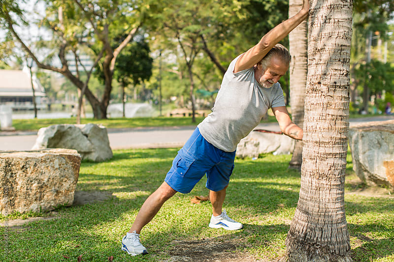 Older Man Stretching in the Park by Mosuno for Stocksy United
