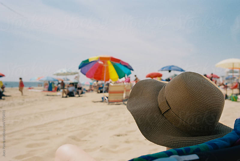Woman in hat on crowded beach during summer, face hidden by Joey Pasco for Stocksy United