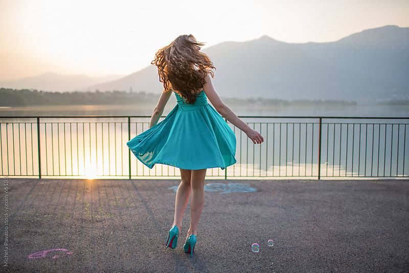 Young woman dancing on a terrace overlooking the lake by michela ravasio for Stocksy United