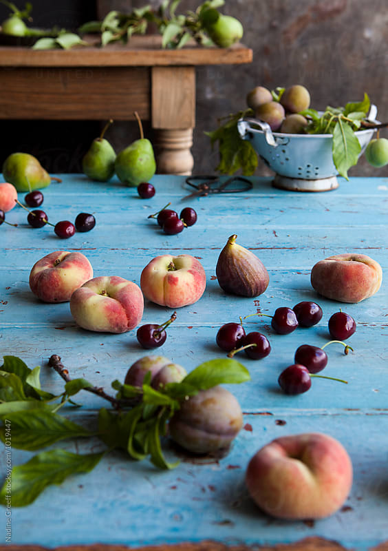 Harvested fruit on kitchen table by Nadine Greeff for Stocksy United