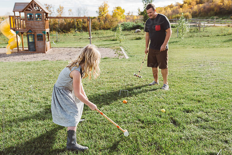 Father and daughter playing croquet by Carey Shaw for Stocksy United