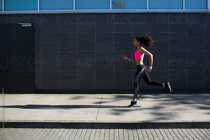 Sporty woman running outdoors by michela ravasio for Stocksy United