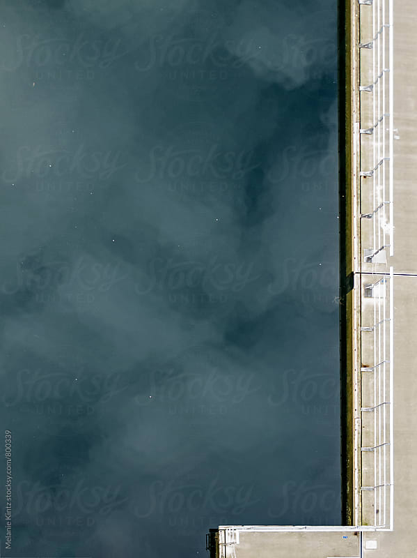 Pier in a lake seen from above by Melanie Kintz for Stocksy United