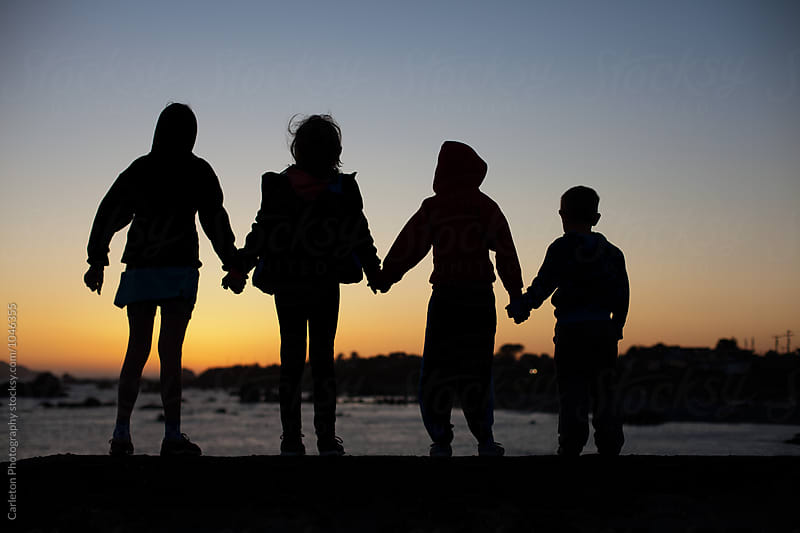 Silhouette of four kids holding hands on the coast at sunset by Carleton Photography for Stocksy United