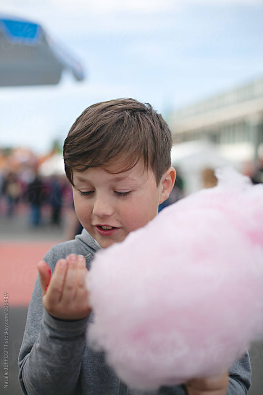 A young boy eating a sugary cloud of sweet cotton candy / fairy floss at the fair by Natalie JEFFCOTT for Stocksy United