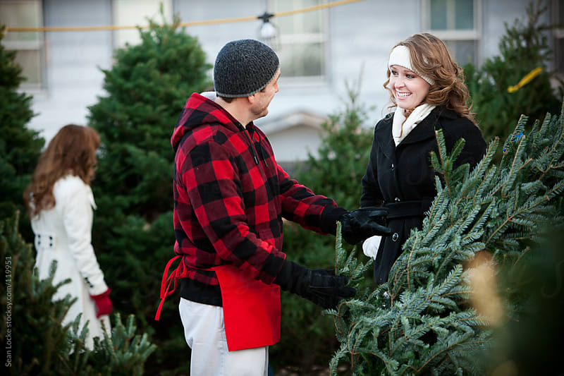 Tree Lot: Employee Helps Woman Pick Out Tree by Sean Locke for Stocksy United