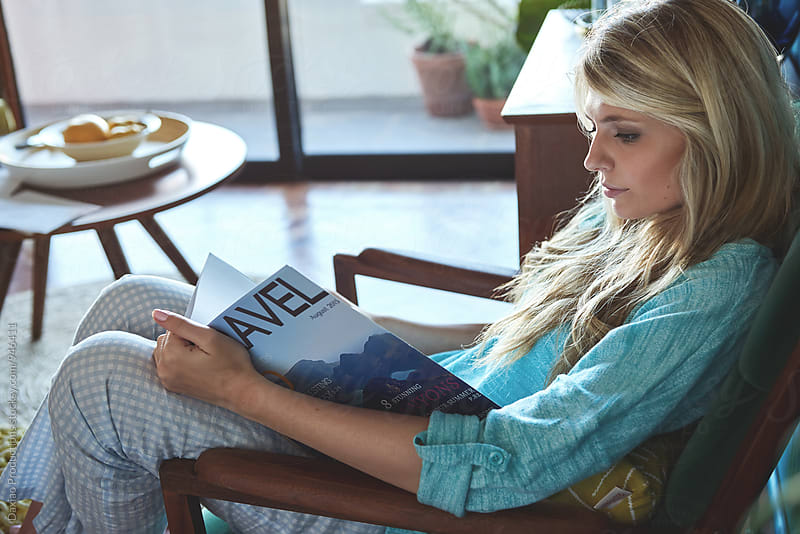 Woman relaxing at home reading a travel magazine  by Daxiao Productions for Stocksy United